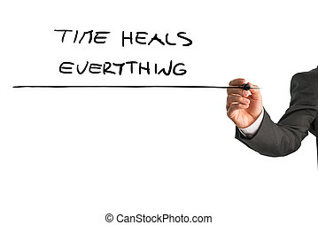Time heals everything - Closeup of male hand writing a ...