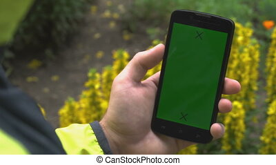 Closeup of male hands holding smartphone with green screen-prekeyed effects. nature in the background