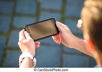 Closeup of male hands is holding cellphone with empty copy space screen for your advertising text message or promotional content. Man using mobile smartphone