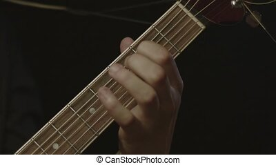 Closeup of male hands playing acoustic guitar