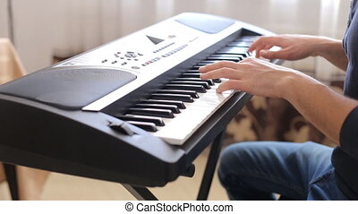 closeup of male hands playing piano. Man Playing the synthesizer keyboard.