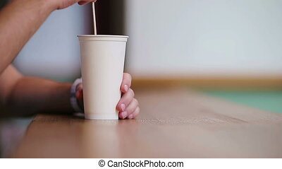 Closeup of male hands stir the sugar in a glass with coffeee in cafe.