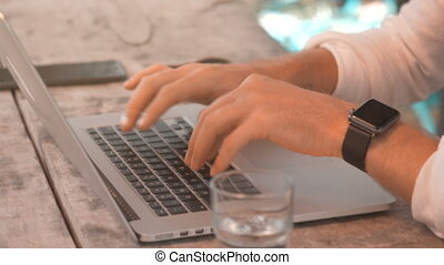 Closeup of male hands typing on laptop