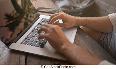 Closeup of male hands typing on laptop in tropical cafe