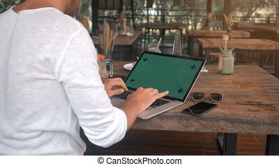 closeup shot of male hands working on a laptop with green screen in cafe