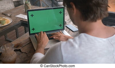 closeup of male hands working on a laptop with green screen in cafe
