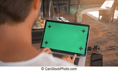 closeup of male hands working on a laptop with green screen...