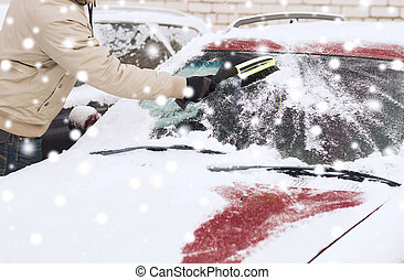 closeup of man cleaning snow from car