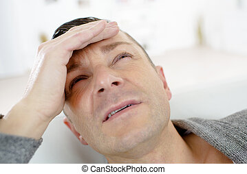Closeup of man holding his head