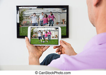 Man Holding Smartphone Connected To A TV