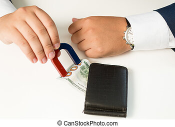 Closeup of man in suit pulling money out wallet with magnet