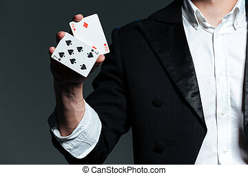 Closeup of man magician holding two playing cards