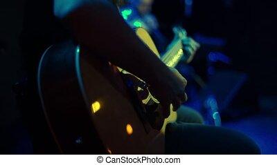closeup of man playing acoustic guitar on rock concert