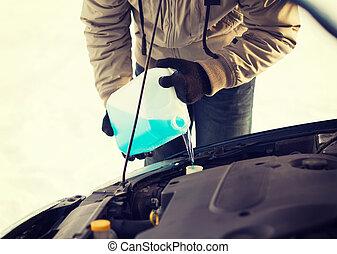 closeup of man pouring antifreeze into water tank -...