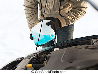 closeup of man pouring antifreeze into water tank -...
