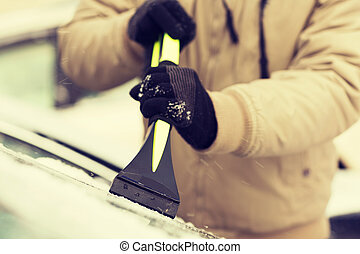 closeup of man scraping ice from car