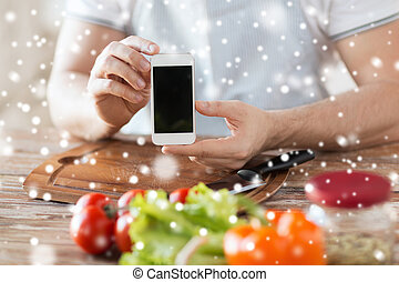 closeup of man showing smartphone in kitchen