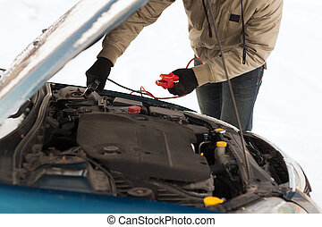 closeup of man under bonnet with starter cables -...