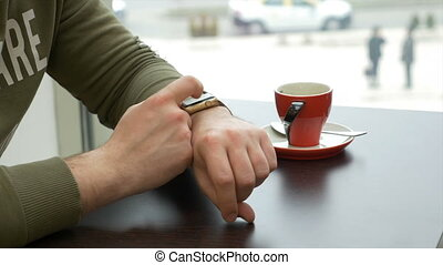 Closeup of man using smartwatch app while sitting at table in a cafe in the city