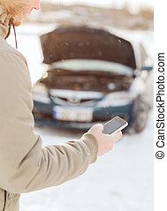 closeup of man with broken car and cell phone -...