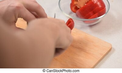 Closeup of man's hand cut red pepper on a cutting Board and put it in a glass bowl