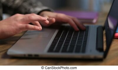 Closeup of man's hands working on laptop