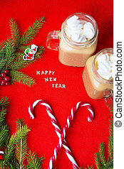 Closeup of marshmellou cocoa and candy on a red background. The inscription Happy New Year!