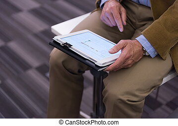 Closeup of mature hands holding tablet.