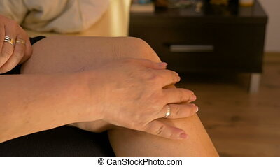 Closeup of mature married woman carefully massaging her rheumatic knee at home in bed