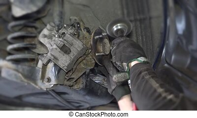 closeup of mechanic worker hands grind rusty car brake system parts with grinder