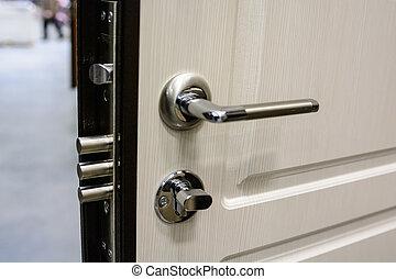 Closeup of metal doorhandle and look on white door