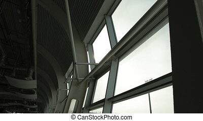 Closeup of metallic architectural constructions at airport inside terminal. View on floodlight, bright sun from glass window.