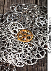 Closeup of metallic cogwheels pile, on wooden surface