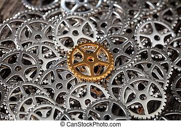 Closeup of metallic cogwheels pile with one bronze