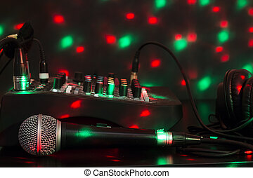 Closeup of microphone, mixing table and headphones with colorful lights.