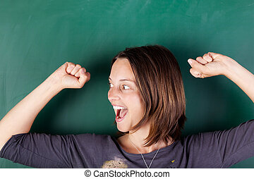 woman with arms raised shouting against chalkboard