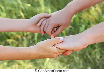 closeup of mother and son hands holding each other, green grass