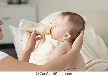 Closeup of mother giving milk from bottle to her baby son sitting on sofa