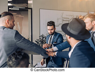 Closeup of multiracial group business men giving high five in office