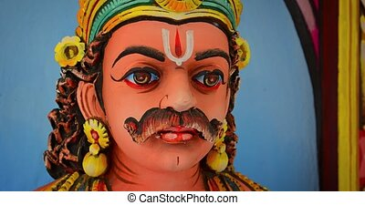 Closeup of a colorful statue depicting a mustachioed deity's face in fine detail, inside a popular Hindu Temple.