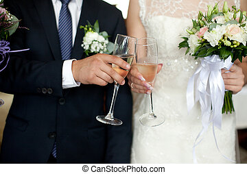 Closeup of newlyweds hands clanging champagne flutes