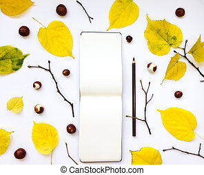 Closeup of notebook and pencil, decorated with autumn yellow leaves and branches. Top view, flat lay