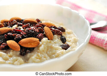 Closeup of nutritious oatmeal topped with rasins and nuts ...