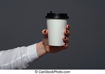 Closeup of office worker holding cup with coffee