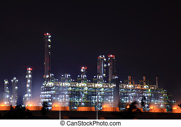 closeup of oil refinery factory at night