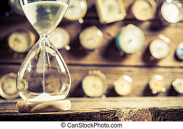 Closeup of old hourglass on clocks background
