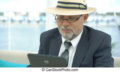 Closeup of old man using tablet and looking on wristwatch at the table.
