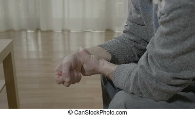 Closeup of old man with arthritis touching his painful wrist having rheumatism sitting on the couch at home
