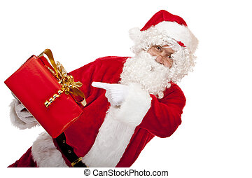 Closeup of old Santa Claus holding a red Christmas gift in one hand and with other hand he points on the present. Isolated on white.