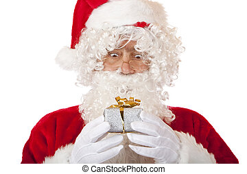 Closeup of old Santa Claus looking surprised on a Christmas present in his hands. Isolated on white.